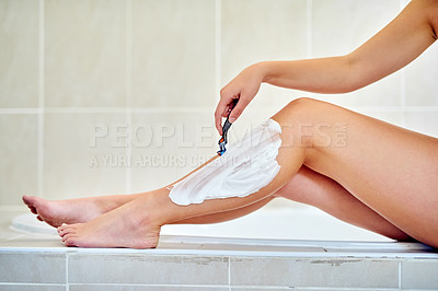 Buy stock photo Closeup shot of an unrecognizable woman shaving her legs in the bathroom at home