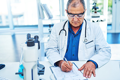Buy stock photo Shot of a mature scientist writing notes while working in a laboratory