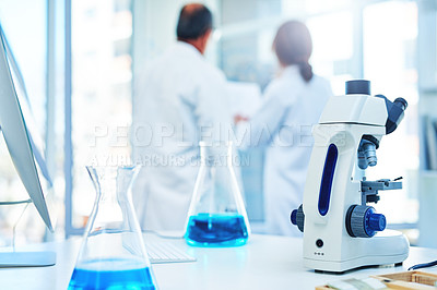 Buy stock photo Shot of a microscope and beakers in a lab with two scientists in the background