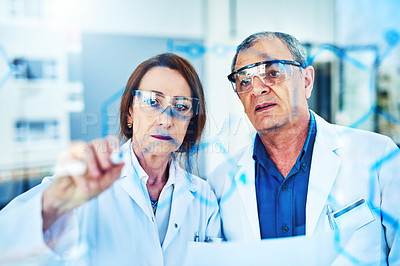 Buy stock photo Shot of two scientists drawing molecular structures on a glass wall in an office