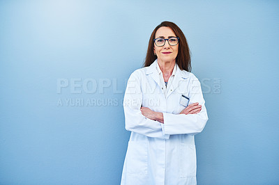 Buy stock photo Studio portrait of a mature scientist standing against a blue background