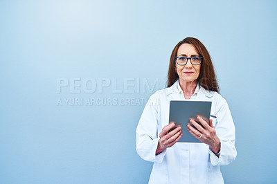 Buy stock photo Studio portrait of a mature scientist using a digital tablet against a blue background