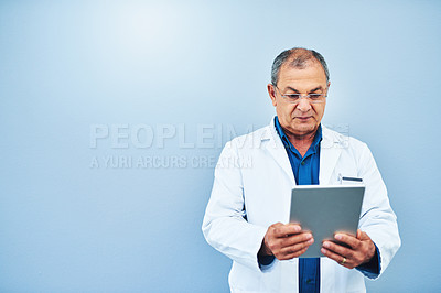 Buy stock photo Studio shot of a mature scientist using a digital tablet against a blue background