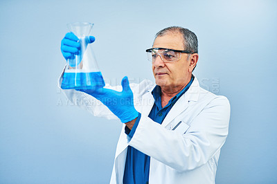 Buy stock photo Studio shot of a mature scientist holding a beaker against a blue background