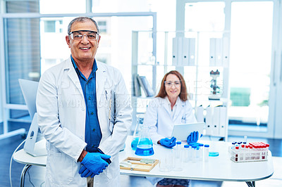 Buy stock photo Portrait of a mature scientist standing in a lab with a colleague in the background