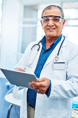Buy stock photo Portrait of a mature scientist using a digital tablet in a laboratory