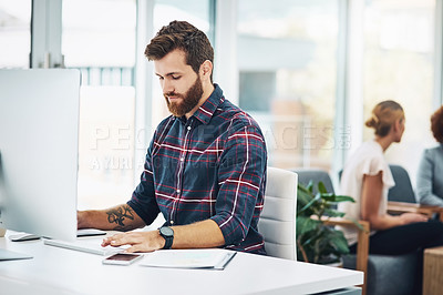 Buy stock photo Shot of a young businessman working in an office with his colleagues in the background