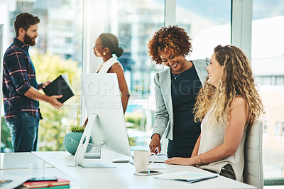 Buy stock photo Shot of two businesswomen working together on a computer in an office with their colleagues in the background