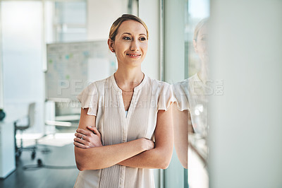 Buy stock photo Shot of a young businesswoman looking through a window in an office