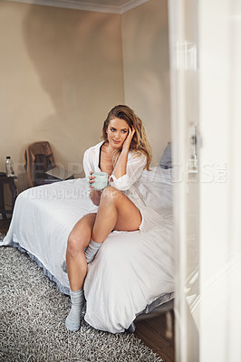 Buy stock photo Shot of a relaxed young woman having coffee in her bedroom at home