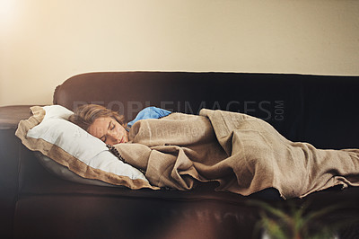 Buy stock photo Shot of a young woman sleeping peacefully on the sofa at home