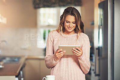 Buy stock photo Shot of a relaxed young woman having coffee and using a smartphone at home