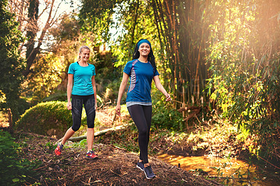 Buy stock photo Shot of two sporty young women out exercising in nature