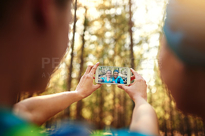 Buy stock photo Shot of two sporty young woman taking pictures while out in nature