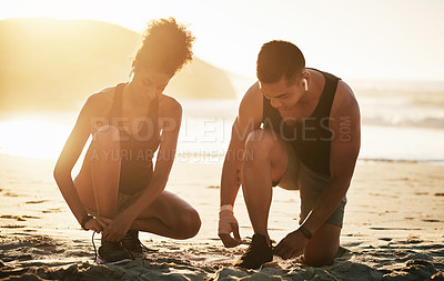 Buy stock photo Shot of a young couple tying their shoelaces while working out at the beach