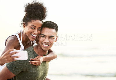 Buy stock photo Shot of a young couple taking selfies while bonding together outdoors