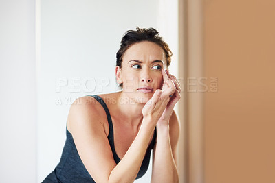 Buy stock photo Cropped shot of an attractive woman squeezing a pimple in front of the bathroom mirror