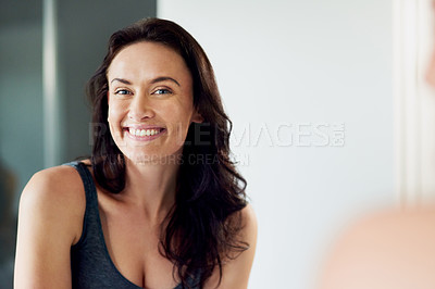 Buy stock photo Cropped portrait of an attractive woman admiring her face in the bathroom mirror