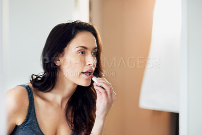 Buy stock photo Cropped shot of a beautiful woman applying lipstick in the bathroom at home