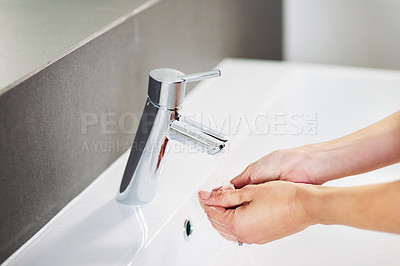 Buy stock photo High angle shot of an unrecognizable woman washing her hands in the bathroom at home