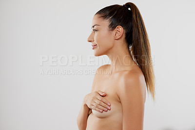 Buy stock photo Studio shot of an attractive young woman covering her breasts while posing against a grey background