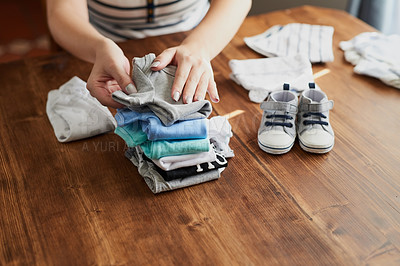 Buy stock photo Cropped shot of a pregnant woman sorting baby clothes at home