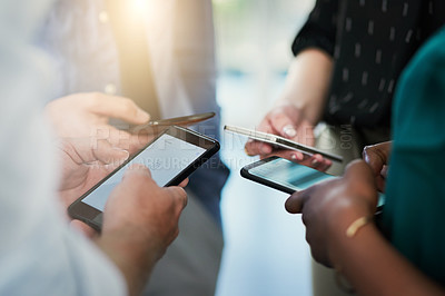 Buy stock photo Cropped shot of a group of businesspeople using their smartphones in a modern office