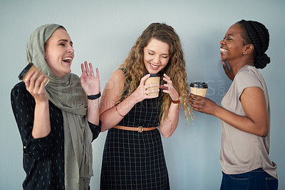 Buy stock photo Studio shot of a group of happy young colleagues having coffee and laughing together against a grey background