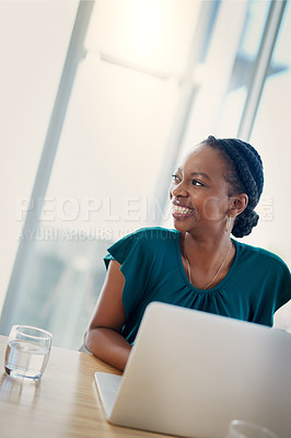 Buy stock photo Shot of a confident young businesswoman working at her desk in a modern office