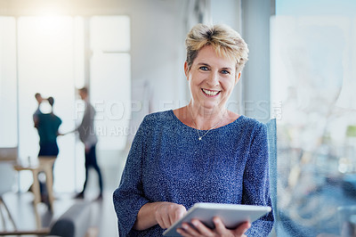 Buy stock photo Portrait of a mature businesswoman using a digital tablet in a modern office