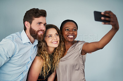 Buy stock photo Studio shot of a group of happy young colleagues taking selfies against a grey background