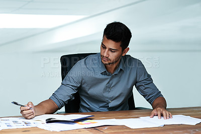 Buy stock photo Cropped shot of a young businessman working at his desk in the office