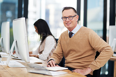 Buy stock photo Shot of a businessman sitting at his desk with his colleague working in the background