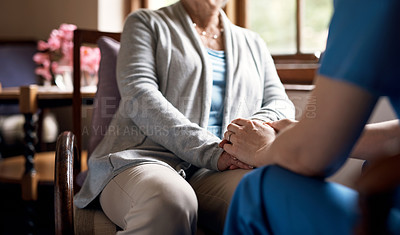 Buy stock photo Cropped shot of a nurse holding hands with an elderly woman in a retirement home