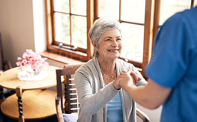 Buy stock photo Shot of a nurse holding hands with an elderly woman in a retirement home