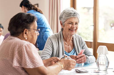 Buy stock photo Shot of a senior woman playing cards in a retirement home during the day
