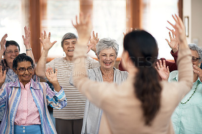 Buy stock photo Rearview shot of a female fitness instructor taking a class in an old age home