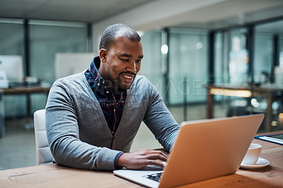 Buy stock photo Shot of a handsome young businessman working on a laptop in his office