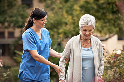 Buy stock photo Shot of a caregiver and her patient out for a walk in the garden