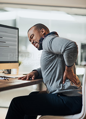 Buy stock photo Shot of a young businessman suffering from a backache while working at his desk in his office