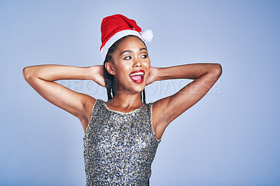 Buy stock photo Studio shot of a beautiful young woman wearing a Christmas hat against a blue background