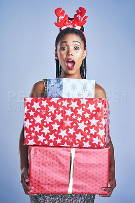 Buy stock photo Studio shot of a young woman holding three gift boxes stacked on top of each other