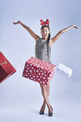 Buy stock photo Studio shot of a young woman throwing gifts while standing against a grey background