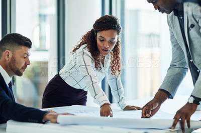 Buy stock photo Shot of a group of businesspeople looking at blueprints in an office