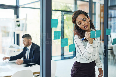 Buy stock photo Shot of a young businesswoman writing notes on a glass wall with her colleague in the background in an office