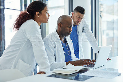 Buy stock photo Shot of a group of medical practitioners working on a laptop together