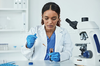 Buy stock photo Shot of a young scientist analyzing samples in a lab