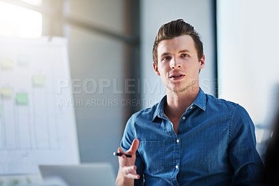 Buy stock photo Shot of a young businessman explaining his ideas to his colleagues in a modern office