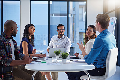 Buy stock photo Shot of a group of young businesspeople discussing ideas with each other during a meeting in a modern office