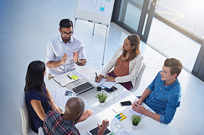 Buy stock photo High angle shot of a group of young businesspeople having a meeting together around a table in a modern office